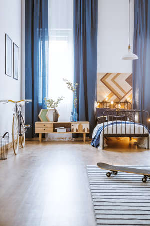 Modern bedroom interior for a teenager with long curtains, bed, skateboard, bicycle, cupboard, posters and lamp Stock Photo