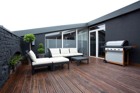 Grill and white garden furniture on wooden floor of terrace with plants and black brick wall