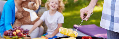 Man preparing yellow sweet corn on the grill for little boy in the park Imagens