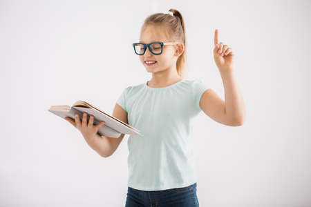 Portrait of a young, smart girl in glasses standing with an open book and pointing with her finger Stock Photo