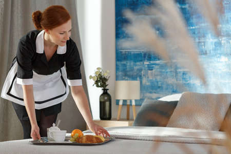 Housemaid putting a tray with food on a hotel room bed in the morning Zdjęcie Seryjne - 98254734