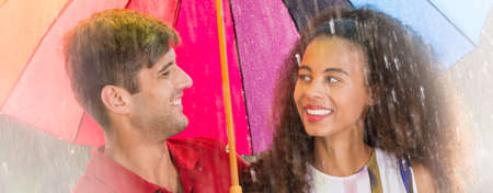 Multicultural couple looking each other in the eyes during summer stroll