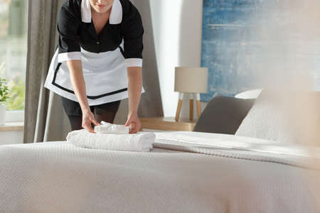 Young maid laying fresh towels on a bed in a hotel room Stock Photo