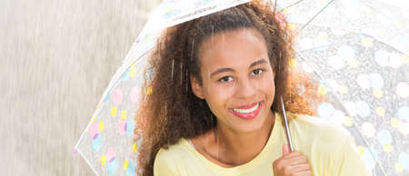 Afroamerican happy woman enjoying heavy summer rain under umbrella