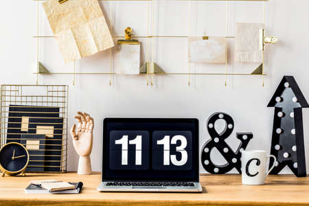 Clock screensaver on a laptop for remote work standing on a wooden desk with notebooks, coffee mug and decor Stock Photo