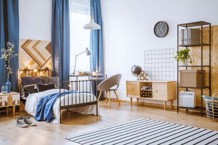 Bright bedroom interior for a boy with a metal bed, wooden cupboard, rug, light decorations, black clock and navy blue curtains Stock Photo