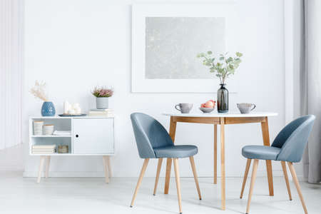 Small dining table with two upholstered chairs and a white cabinet in a bright, open space living room interior Stockfoto