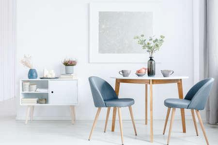 Pequeña mesa de comedor con dos sillas tapizadas y un gabinete blanco en el interior de una sala de estar luminosa y abierta. Foto de archivo