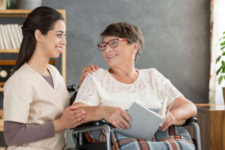 Old, happy woman in a wheelchair reading a book with a nurse Banque d'images - 98893748