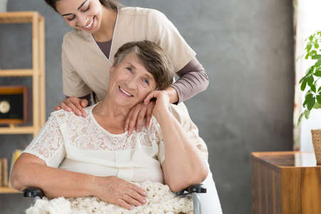 Happy nurse taking care of a senior woman in a wheelchair
