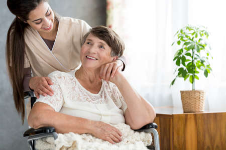 Senior smiling woman sitting in a wheelchair and talking to a nurse in a room with a plant Stock Photo