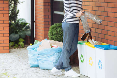 Close-up of aware person segregating household waste on the terrace