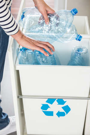 High angle of a person segregating plastic bottles in the kitchen