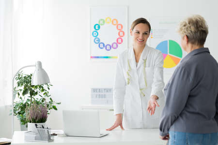 Smiling dietitian in white uniform inviting a patient with diabetes for dietary consultation Stock Photo
