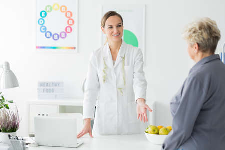 Happy dietitian with measure tape inviting a woman for dietary consultation