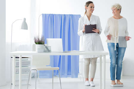 Happy woman standing on a scale during meeting with smiling dietician in white uniform