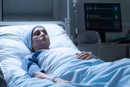 Middle-aged woman with cancer dying alone in a palliative ward of a hospital and heart rate monitor in the background