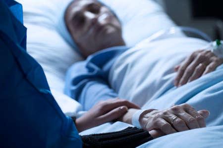 Młoda kobieta żegna się z matką umierającą na raka w hospicjum, trzymając ją za rękę