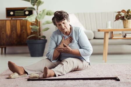 Lonely elderly woman having a heart attack, sitting on the floor at home