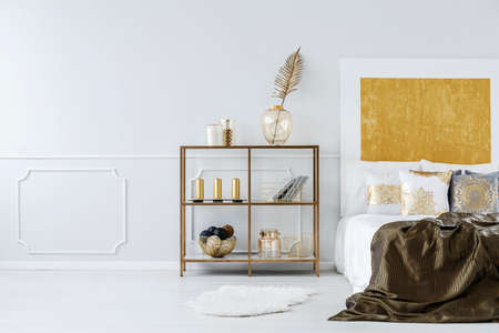 Golden bedroom interior with bed, metal shelf and wall molding