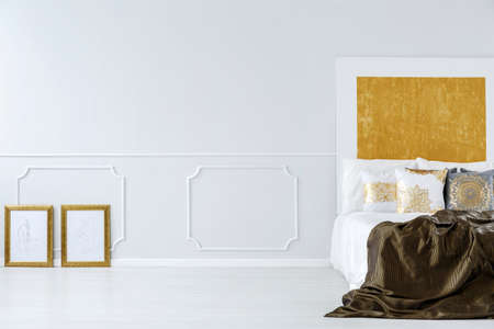 Hotel room interior with bed, wall molding and golden accents