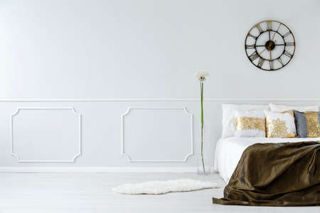 Metal clock on the wall in bedroom interior with king size bed and golden pillows