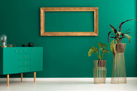 Plants in tall, golden stands, a teal cabinet and an empty, luxurious frame on a green wall of a modern apartment interior