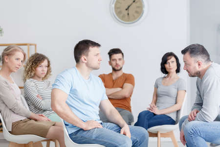 Angry young man sitting in a chair and confronting his father in group therapy