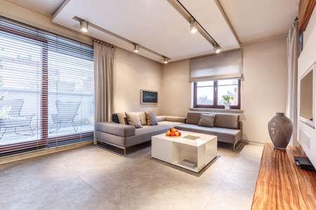 Ciepłe, luksusowe wnętrze salonu z beżowymi ścianami i marmurowymi podłogami, białym stolikiem kawowym i dużym, szarym narożnikiem z poduszkami
