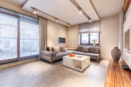 Intérieur de salon chaleureux et luxueux avec des murs et des sols en marbre beiges, une table basse blanche et un grand canapé d'angle gris avec des oreillers
