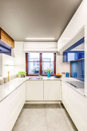 Small, bright kitchen interior with a window in the center, elegant countertop and modern, blue glass elements