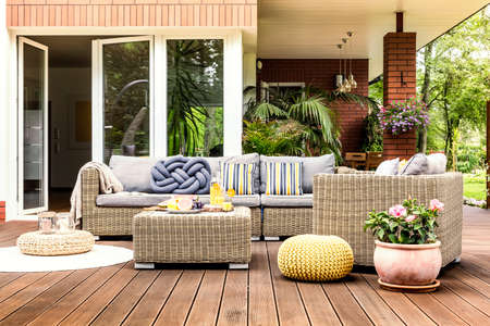 Muebles de jardín de color beige con almohadas a rayas en una terraza de madera con flores de color rosa y pufs