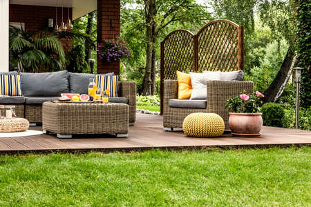 Yellow pouf next to pink flowers on wooden terrace with rattan armchair, table and sofa