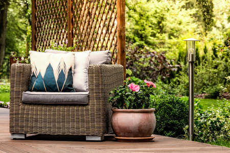 Pink flowers next to a rattan armchair with decorative pillows on wooden terrace 写真素材