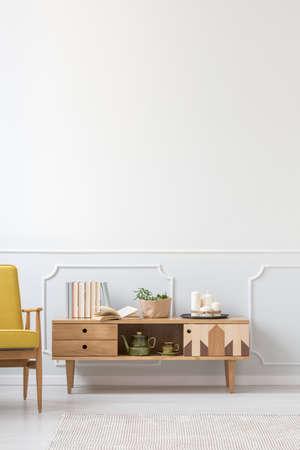 Libri sull'armadietto di legno contro la parete grigia del modanatura con lo spazio della copia nell'interno minimalista del salone Archivio Fotografico - 98870663