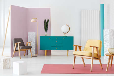 Turquoise cabinet in room interior with armchairs, cubes and movable wall Reklamní fotografie