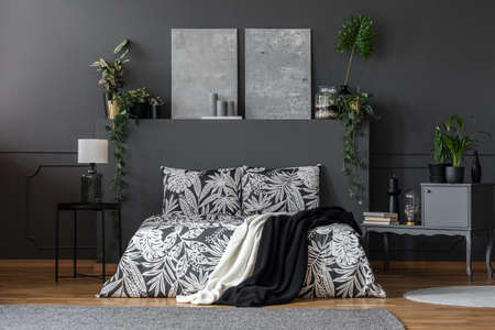 Two black and white blankets thrown on king-size bed with floral bedclothes standing in dark room interior with green plants and candles