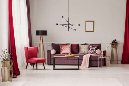 Red armchair and wooden lamp near violet sofa in spacious living room interior with mockup Stock Photo