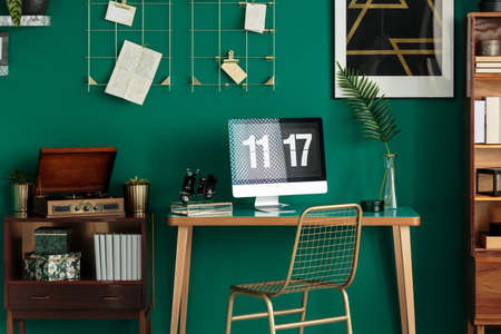 Green living room interior with home office desk standing next to a cupboard with vintage gramophone Stock Photo