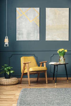 Gelber Lehnsessel zwischen einer Anlage auf einem Weidenhocker und einem Beistelltisch mit Tulpen und einem offenen Buch in einem dunklen Wohnzimmerinnenraum mit einer grauen Wolldecke