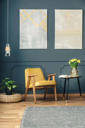 Yellow armchair between a plant on a wicker ottoman and a side table with tulips and an open book in a dark living room interior with a gray rug