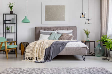 Upholstered double fabric bed with cozy blankets and pillows in a bright, modern interior with pastel furniture and decor Stock Photo
