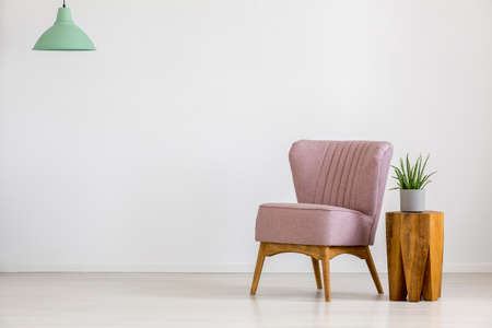 Retro chair with pastel pink upholstery and a wooden table in an empty room interior with white walls and copy space Standard-Bild