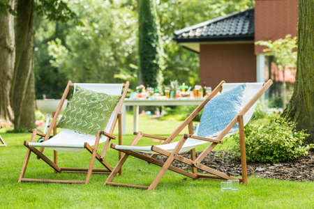 Two sunbeds with green and blue patterned pillow stand in the garden on a sunny day