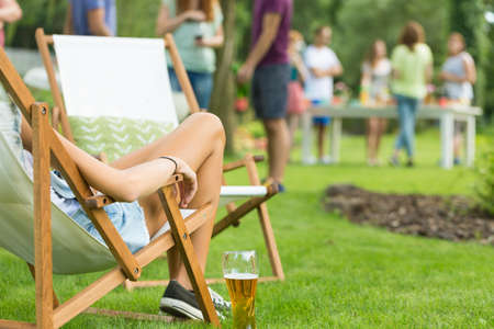 Close-up of beautiful young womans legs, girl enjoying summer vacation, relaxing while sitting on deck chair with beer, friends at garden party in the background