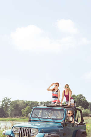 カブリオレで一般的な夏の旅行を楽しむ友人 写真素材