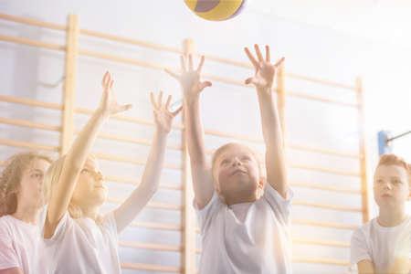 体育の授業中にバレーボールをするアクティブな子供たちの低角度 写真素材