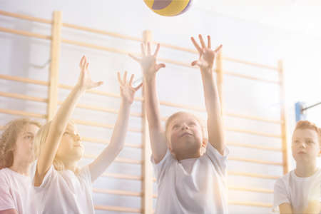 Low angle of active children playing volleyball during physical education classes