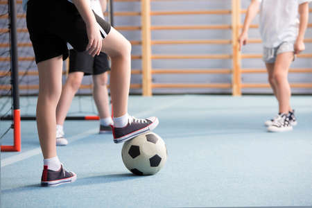 Close-up of boys playing football at school during physical education classes Stock Photo