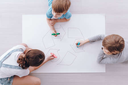 Kids sitting on the floor and drawing a poster of recycling sign